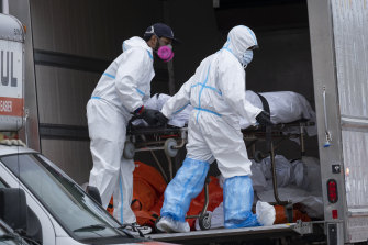 Workers move bodies to a refrigerated truck in New York in April. Virus deaths in the US have now passed 200,000.