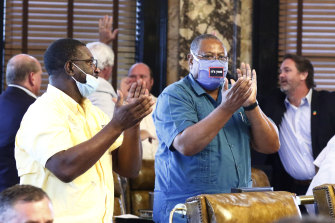 Democratic senators Juan Barnett and Robert Jackson applaud while their colleagues give each other high-fives after the Mississippi Senate passed a resolution that would allow lawmakers to change the state flag.