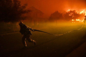 A firefighters drags a hose as he defends the Skyhawk Park neighbourhood of East Santa Rosa.