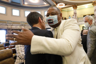 Senator Briggs Hopson is hugged by Senator Robert Jackson after the Senate voted to change the state flag.