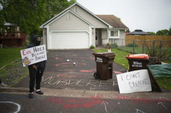 A protester stands outside Derek Chauvin's house in May 2020.