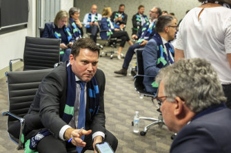 FFA chief executive James Johnson passes his phone to chairman Chris Nikou as they wait for FIFA to announce the hosts of the 2023 Women's World Cup.