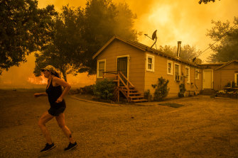 A woman races across her property as the LNU Lightning Complex fire approaches in Vacaville, California.