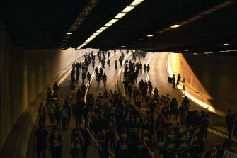 Demonstrators crowd a road during a protest in the Tsim Sha Tsui area of Kowloon, Hong Kong, on December 1.
