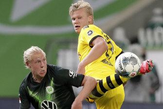Wolfsburg's Xaver Schlager vies for the ball with Dortmund's Erling Haaland.