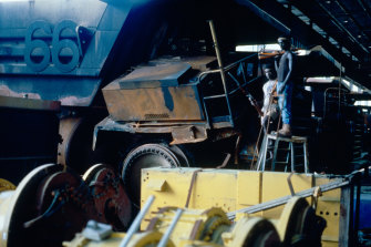 Bougainville Revolutionary Army guerillas stand next to a destroyed dump truck at  Panguna mine in 1994.