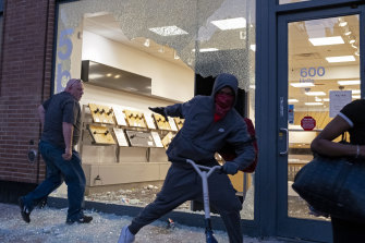 A store is damaged in the Chelsea neighborhood of New York as looters grabbed merchandise along the street.