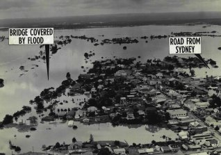 The road from Sydney (extreme right) And the Nepean bridge (extreme left) are covered in this aerial picture showing the flooding at Windsor. November 22, 1961.