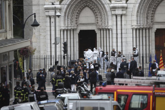 Police officers work at the Notre Dame church in Nice, southern France, after the attack.