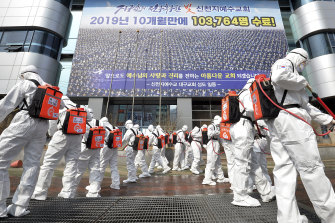 Soldiers in protective suits spray disinfectant on the steps of the Shincheonji Church of Jesus in South Korea.