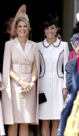 Queen Maxima of the Netherlands and the  Duchess of Cambridge stand together as they watch the annual Order of the Garter Service at St George's Chapel, Windsor Castle.