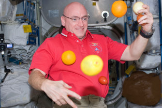 A photo provided by NASA shows astronaut Scott Kelly with fresh fruit aboard the International Space Station in 2010.