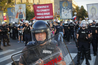Serbian riot policemen prevent anti-gay protesters, seen holding religious banners in the background, from clashing with participants in the annual gay pride march in Belgrade, Serbia.