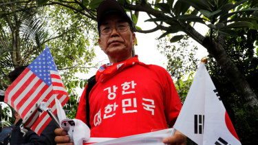 A South Korean man holds American and North Korean flags as he calls for an improvement in the human rights situation in North Korea near the Capella hotel on Sentosa island in Singapore on Tuesday.
