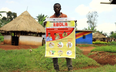 A man displays an Ebola information leaflet in Mangina, Democratic Republic of the Congo.