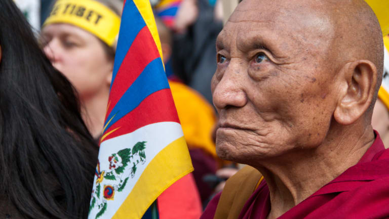 Palden Gyatso with a Tibetan flag at the Tibet Freedom March in London in 2015, the 50th anniversary of the Tibetan People's Uprising.