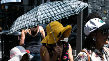 A person holds an umbrella for shade in  Times Square.