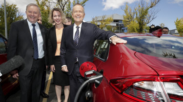 Anthony Albanese, Labor candidate for Canberra Alicia Payne and Bill Shorten view an electric car at a charging station.