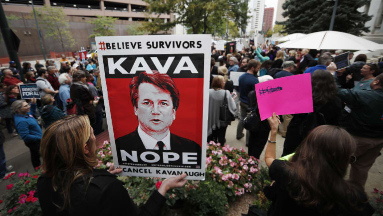 A woman holds a placard during a protest against the nomination of Brett Kavanaugh for the Supreme Court, in Denver, Colorado.