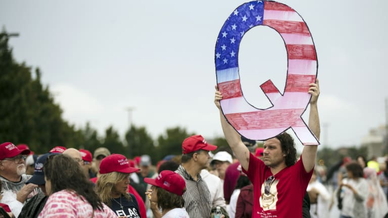 Trump supporter David Reinert holds a Q sign waits in line with others to enter a rally with President Donald Trump in Wilkes-Barre, Pennsylvania.