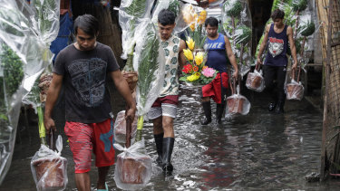 Workers carry plastic plants over flooded waters as heavy monsoon rains continue in Manila, Philippines.