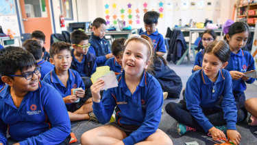 Students at Wheelers Hill Primary School, whose teacher Tim Lee has made up a currency to use in class.