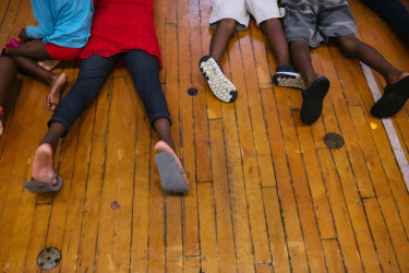 A group of children, who are part of a sudden influx of asylum seekers arriving in Portland, Maine, play in a makeshift shelter.