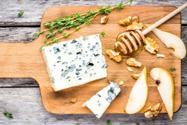 Blue cheese with slices of pear, nuts and honey on wooden cutting board Blue cheese on a cheese board with fruit and honey.