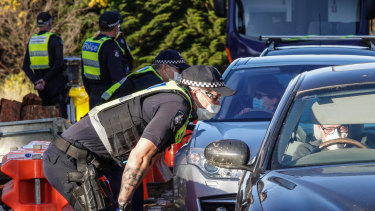 Victoria Police members stop motorists leaving metropolitan Melbourne on Sunday.