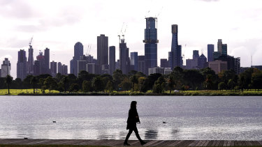 People walk around Albert Park Lake as storm clouds hover over the city skyline in Melbourne yesterday.