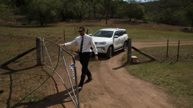 A police detective at the gate of the remote Doyles Creek property on Friday.