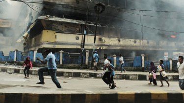 People flee as a local market in Fakfak burnt on Wednesday.