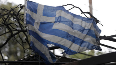 A tattered and charred Greek national flag hangs from a burned-out house in Mati east of Athens.