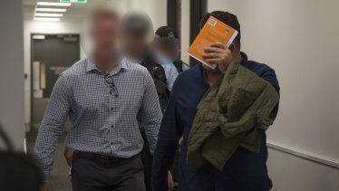 Maythem Radhi is taken into custody at Brisbane Airport.