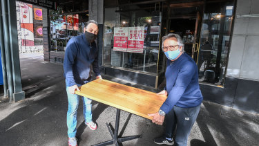 Tiamo's Fab Succi (left) and manager Giulio Damante setting up a table outside their restaurant for the first time in months.