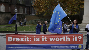 An anti-Brexit supporter holds a European flag by a banner across the street from the Houses of Parliament in London.