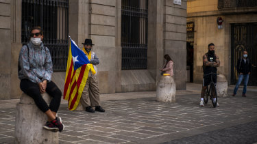 "A man holding an ""estelada"" or independence flag waits for a protest to condemn a police raid on Catalan separatists in Barcelona, Spain."