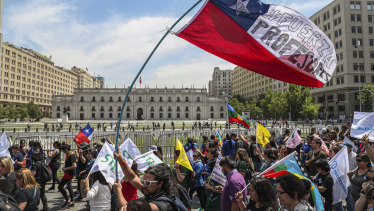 "A teacher marches with a Chilean flag covered with the Spanish message: ""Be strong, teachers"" as protests continue in Santiago on Monday."