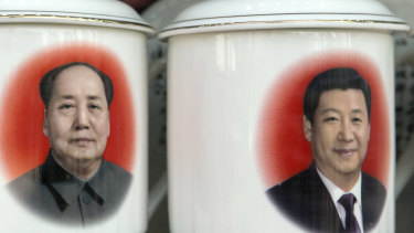 Porcelain cups featuring portraits of former Chinese leader Mao Zedong and current President Xi Jinping in a store window in Beijing.