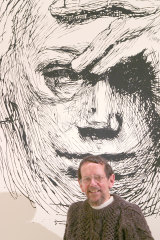 Robert Smith in front of an enlarged copy of a Kathe Kollwitz etching.