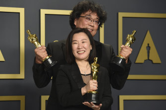 Kwak Sin Ae, front, and Bong Joon Ho, winners of the award for best picture for Parasite. pose in the press room.