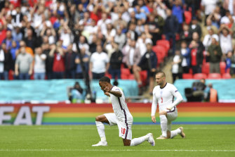 England's Raheem Sterling, left and  Luke Shaw take the knee during the Euro 2020 match between England and Germany at Wembley Stadium in London on June 29.