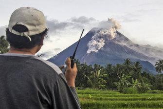A volunteer monitors Mount Merapi during an eruption.