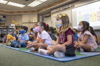 Children listen to their teacher during their first day of transitional kindergarten at Tustin Ranch Elementary School in California.