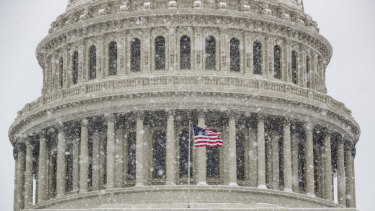An American flag waves in front of the US Capitol Dome as a winter storm arrives in the region on Sunday.