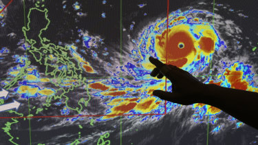 Filipino forecaster Meno Mendoza illustrates the path of typhoon Mangkhut.