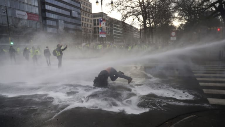 A water cannon is used on a yellow jacket protester in Brussels.