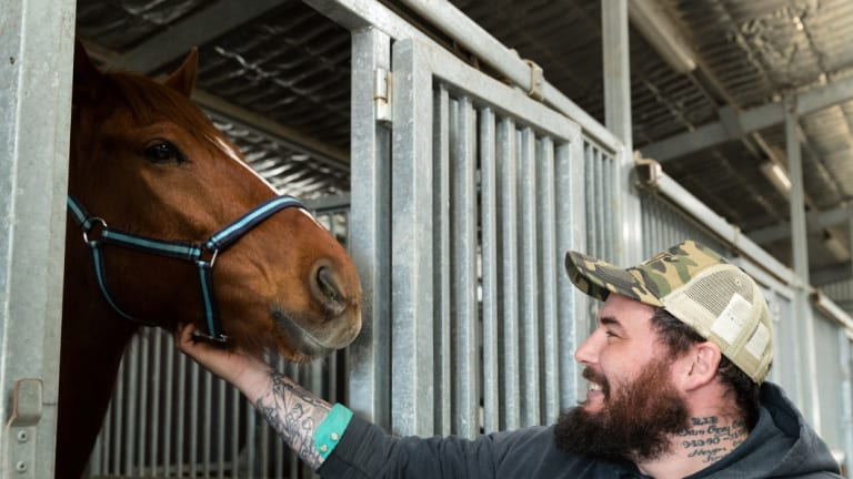 "Returned serviceman Clayton Hellyer with retired racehorse Vashka ... ""People think we save them. They saved me."""