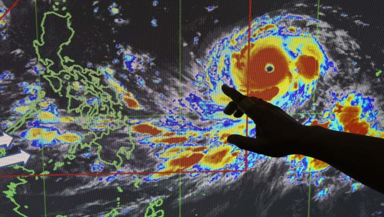 Filipino forecaster Meno Mendoza illustrates the path of typhoon Mangkhut.
