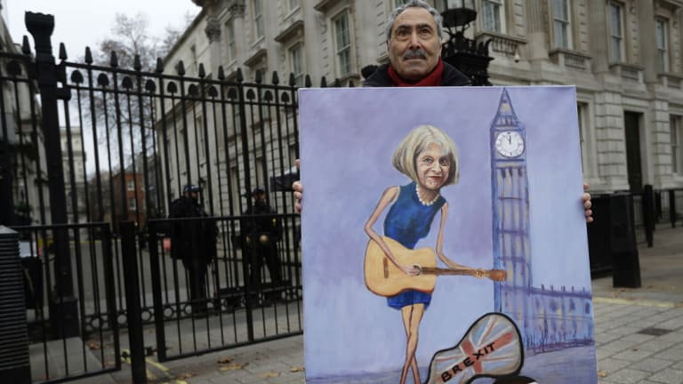 Weird times: Artist Kaya Mar displays his painting of British PM Theresa May in front of Downing Street in London on Tuesday.